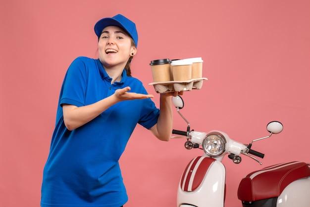 Vue avant femme courrier avec livraison de café sur le travail de livraison de travail rose vélo travailleur uniforme