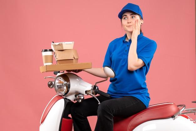 Vue avant femme courrier avec des paquets de nourriture et des boîtes sur la couleur de service uniforme de travail vélo livraison rose