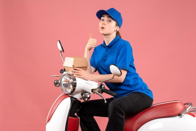 Vue avant femme courrier avec petit paquet de nourriture sur un travail rose couleur travailleur livraison alimentaire service uniforme de vélo