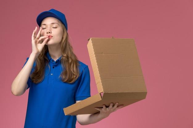 Vue avant femme courrier en uniforme bleu tenant la boîte de livraison de nourriture sur fond rose travail de l'entreprise uniforme de service travailleur