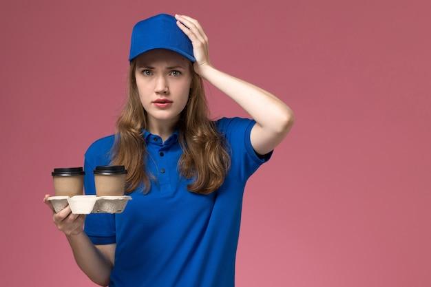 Vue avant femme courrier en uniforme bleu tenant des tasses de café marron sur l'uniforme de service de plancher rose offrant des emplois de l'entreprise