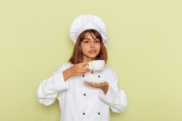 Vue avant femme cuisinier en costume de cuisinier blanc, boire du thé sur une surface verte