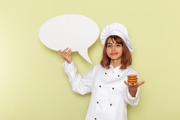 Vue avant femme cuisinier en costume de cuisinier blanc tenant de petits cookies et panneau blanc sur la surface verte