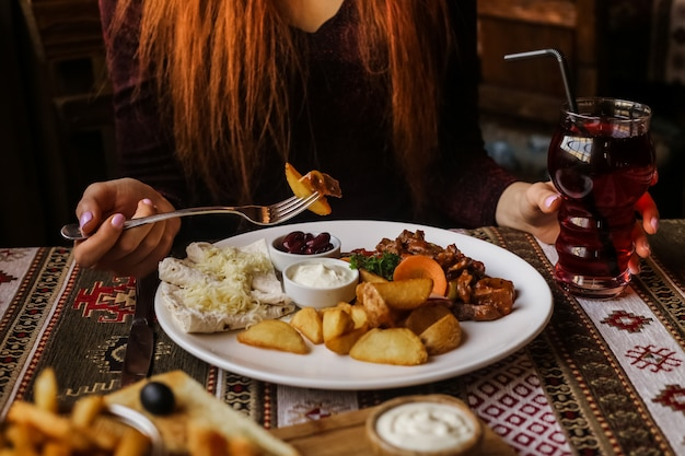 Vue avant femme mangeant de l'igname frite en sauce avec pommes de terre frites, pain pita et sauces sur une assiette avec du jus sur la table