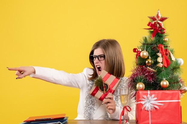 Vue avant femme médecin assis devant sa table tenant présent sur un bureau jaune avec arbre de noël et coffrets cadeaux