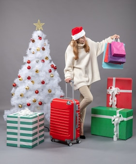 Vue avant de la femme de noël avec bonnet de noel tenant valise rouge et sacs à provisions