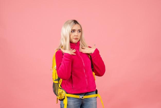 Vue avant femme voyageur dans des vêtements décontractés portant sac à dos pointant sur elle-même