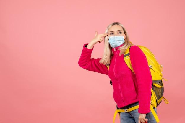 Vue avant femme voyageur avec sac à dos jaune portant un masque mettant le doigt sur sa tempe