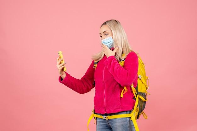 Vue avant femme voyageur avec sac à dos jaune portant un masque de prendre une photo avec son téléphone