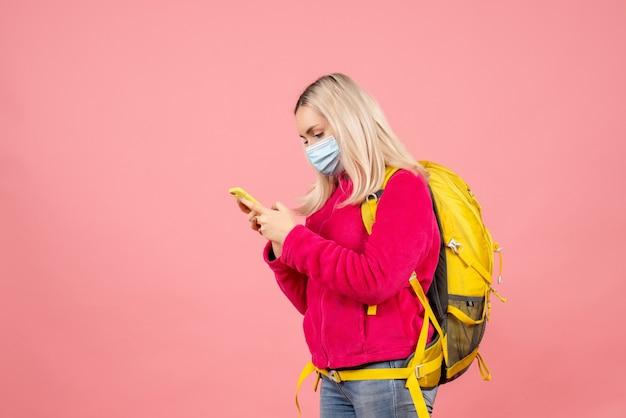 Vue avant femme voyageur avec sac à dos jaune portant un masque à la recherche de téléphone