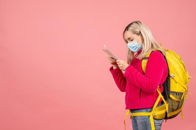 Vue avant femme voyageur avec sac à dos jaune portant un masque en regardant la carte