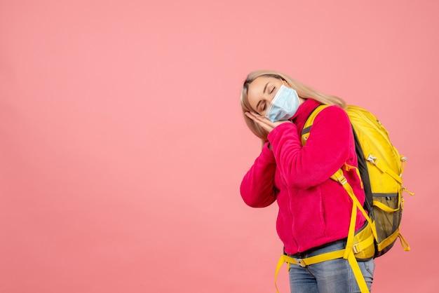 Vue avant femme voyageur avec sac à dos jaune portant un masque de sommeil