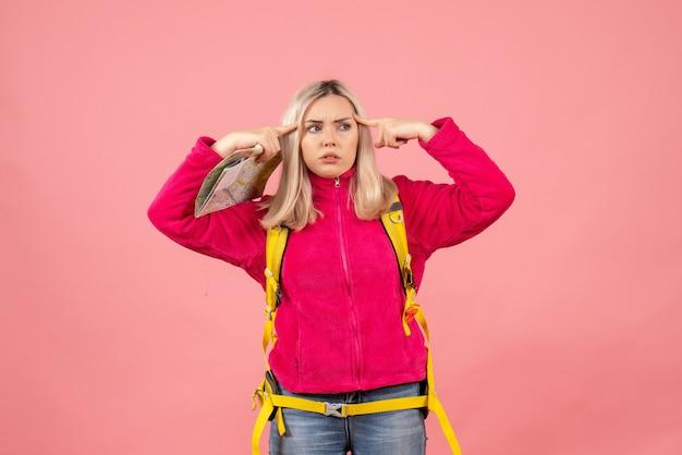 Vue avant femme voyageur avec sac à dos jaune tenant la carte mettant les doigts sur sa tempe