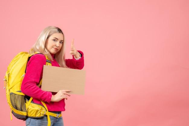 Vue avant femme voyageur avec sac à dos mettant le pistolet à doigt à la caméra tenant le carton