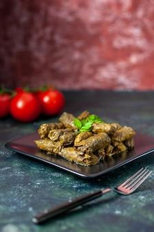 Vue avant de la feuille savoureuse dolma avec des tomates sur le fond sombre de l'huile de calories dîner plat de salade alimentaire repas de restaurant de viande