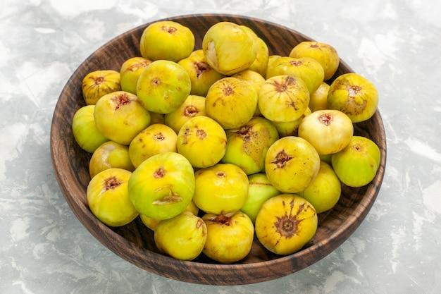 Vue avant des figues sucrées fraîches à l'intérieur de la plaque brune sur un bureau léger