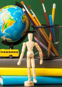 Vue avant de la figurine en bois avec autobus scolaire et globe