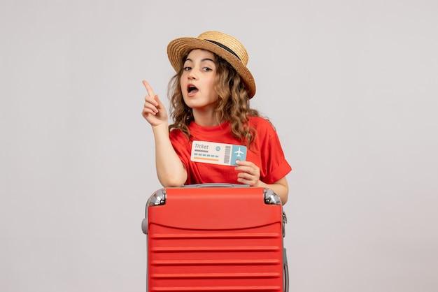 Vue avant de la fille de vacances avec sa valise tenant un billet surprenant avec une idée
