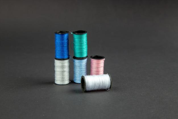 Vue avant des fils colorés sur la surface sombre de l'obscurité de la couture de la broche de mesure de la couleur de la photo