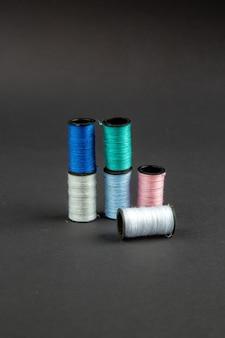 Vue avant des fils colorés sur la surface sombre de l'obscurité de la couture de la broche de mesure des couleurs de la photo
