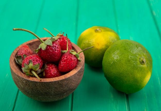 Vue avant des fraises dans un bol et des mandarines sur un mur végétal