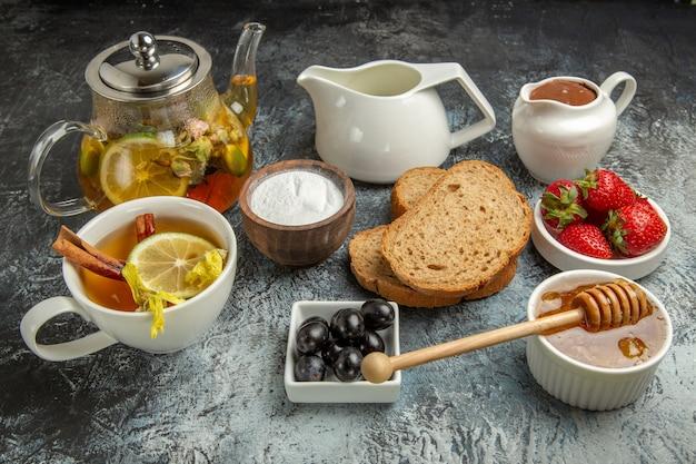 Vue avant des fraises fraîches avec du pain au thé et du miel sur la surface sombre des aliments sucrés de fruits