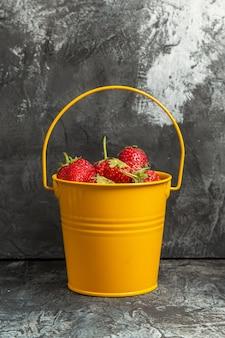 Vue avant des fraises fraîches à l'intérieur du panier sur fond sombre