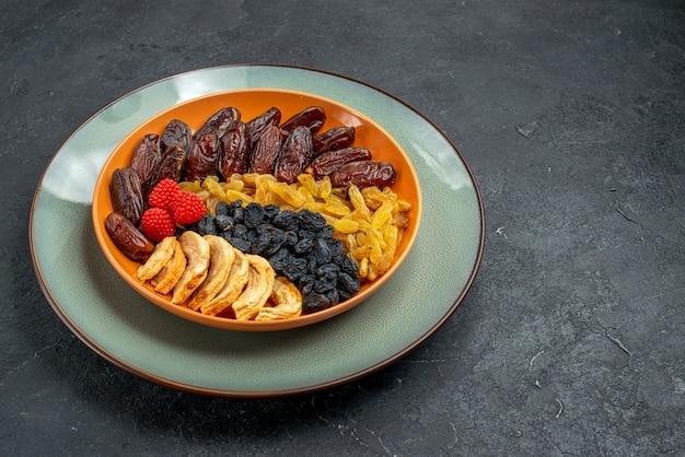 Vue avant des fruits secs avec des raisins secs à l'intérieur de la plaque sur un espace gris foncé