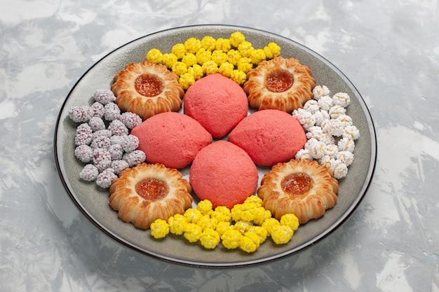 Vue avant des gâteaux roses avec des bonbons et des cookies à l'intérieur de la plaque sur une surface blanche