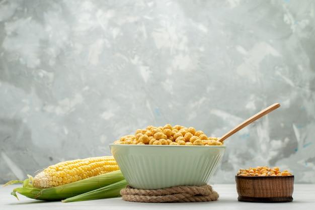 Vue avant des graines de maïs de couleur jaune avec des céréales à l'intérieur de la plaque sur tout le maïs fond blanc