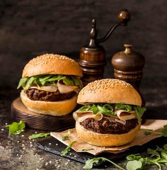 Vue avant des hamburgers de boeuf avec bacon sur ardoise