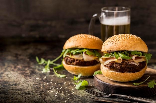Vue avant des hamburgers de boeuf frais avec du bacon et de la bière