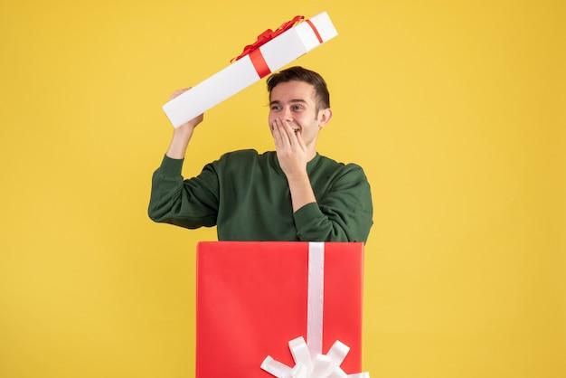 Vue avant heureux jeune homme avec couvercle de boîte debout derrière une grande boîte-cadeau sur jaune