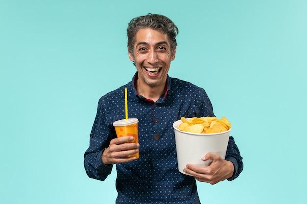 Vue avant, homme d'âge moyen, tenant des cips de pommes de terre et soda en riant sur une surface bleue