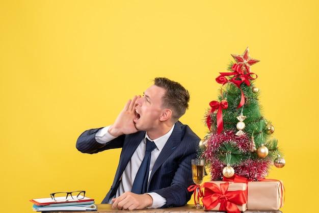 Vue avant de l'homme en colère appelant quelqu'un assis à la table près de l'arbre de noël et des cadeaux sur fond jaune