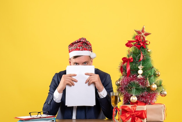Vue avant de l'homme indiscret tenant des documents assis à la table près de l'arbre de noël et présente sur jaune