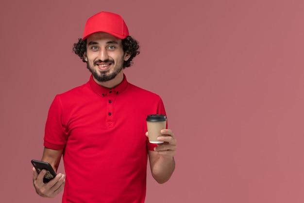Vue avant de l'homme de livraison de messagerie en chemise rouge et cape tenant une tasse de café de livraison marron et à l'aide de téléphone sur mur rose clair employé de livraison
