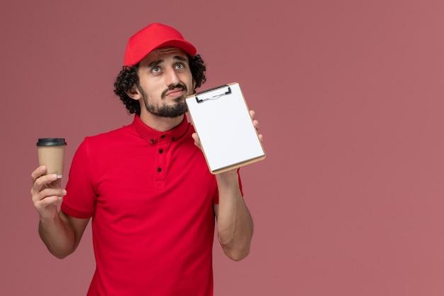 Vue avant de l'homme de livraison de messagerie en chemise rouge et cape tenant une tasse de café marron et bloc-notes en pensant sur le mur rose clair employé de livraison uniforme de service