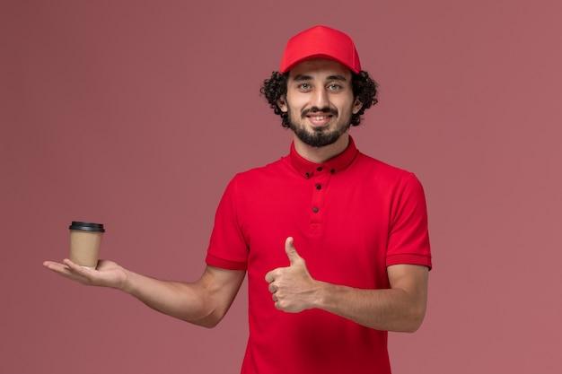 Vue avant de l'homme de livraison de messagerie en chemise rouge et cape tenant une tasse de café marron sur le mur rose service de livraison uniforme de travail des employés
