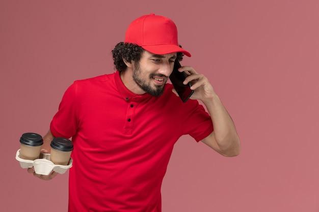 Vue avant de l'homme de livraison de messagerie en chemise rouge et cape tenant des tasses de café de livraison marron et parler au téléphone sur le travail des employés de livraison de services mur rose clair