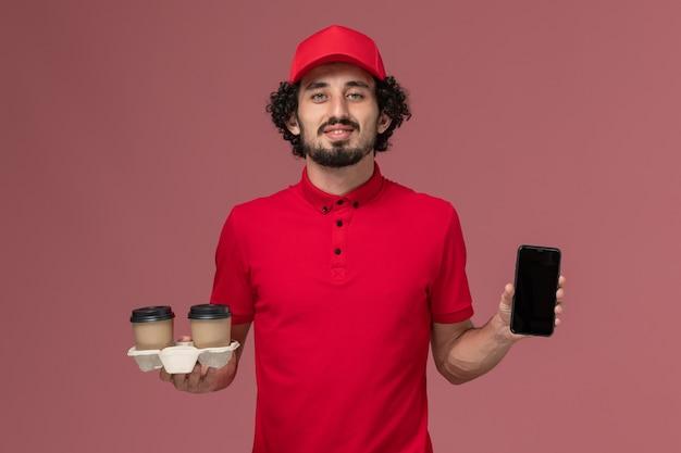 Vue avant de l'homme de livraison de messagerie en chemise rouge et cape tenant des tasses de café de livraison marron et téléphone sur le mur rose clair employé de livraison