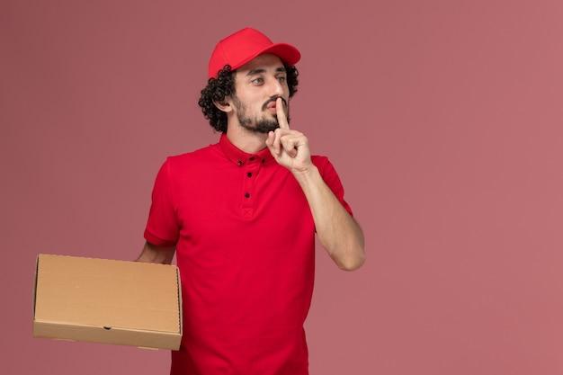 Vue avant de l'homme de livraison de messagerie homme en chemise rouge et cape tenant la boîte de nourriture de livraison sur le mur rose service travail employé de l'entreprise de livraison