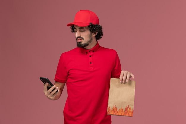 Vue avant de l'homme de livraison de messagerie homme en chemise rouge et cape tenant le paquet de nourriture à l'aide de téléphone sur le mur rose travail des employés de livraison