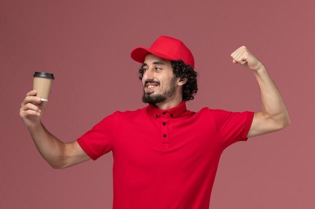 Vue avant de l'homme de livraison de messagerie homme en chemise rouge et cape tenant une tasse de café brun fléchissant sur le mur rose clair employé de livraison uniforme de service