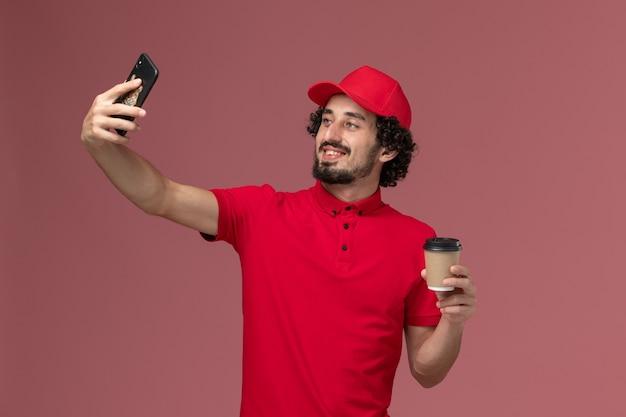 Vue avant de l'homme de livraison de messagerie homme en chemise rouge et cape tenant une tasse de café de livraison brune prenant selfie sur mur rose employé de livraison de services