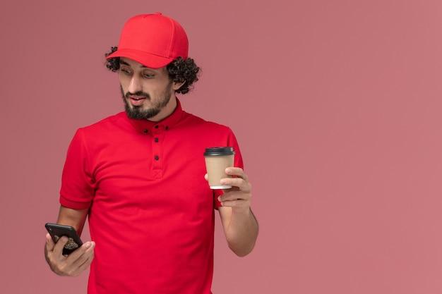 Vue avant de l'homme de livraison de messagerie homme en chemise rouge et cape tenant la tasse de café de livraison marron et téléphone sur mur rose clair service de livraison employé travailleur emploi