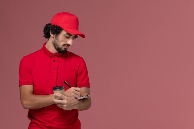 Vue avant de l'homme de livraison de messagerie homme en chemise rouge et cape tenant une tasse de café marron et bloc-notes écrit sur le mur rose clair employé de livraison de services