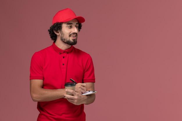 Vue avant de l'homme de livraison de messagerie homme en chemise rouge et cape tenant une tasse de café marron et bloc-notes sur mur rose clair employé de livraison de services