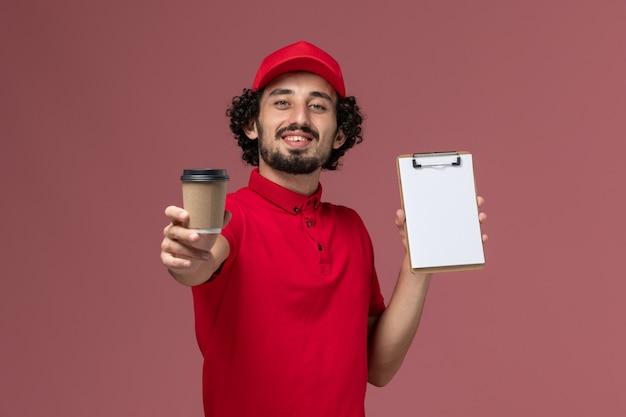 Vue avant de l'homme de livraison de messagerie homme en chemise rouge et cape tenant une tasse de café marron et bloc-notes sur le mur rose clair service de livraison uniforme employé emploi masculin