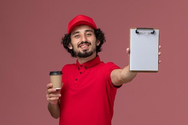Vue avant de l'homme de livraison de messagerie homme en chemise rouge et cape tenant une tasse de café marron et bloc-notes sur le mur rose clair service de livraison uniforme employé travail